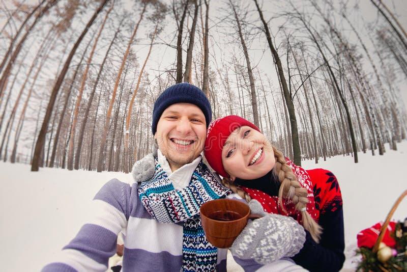 Пары в влюбленности делая selfie на пикнике зимы на парке стоковое изображение rf