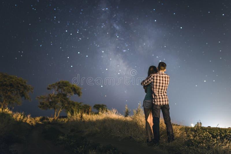 Пары в влюбленности под звездами галактики млечного пути стоковые фото