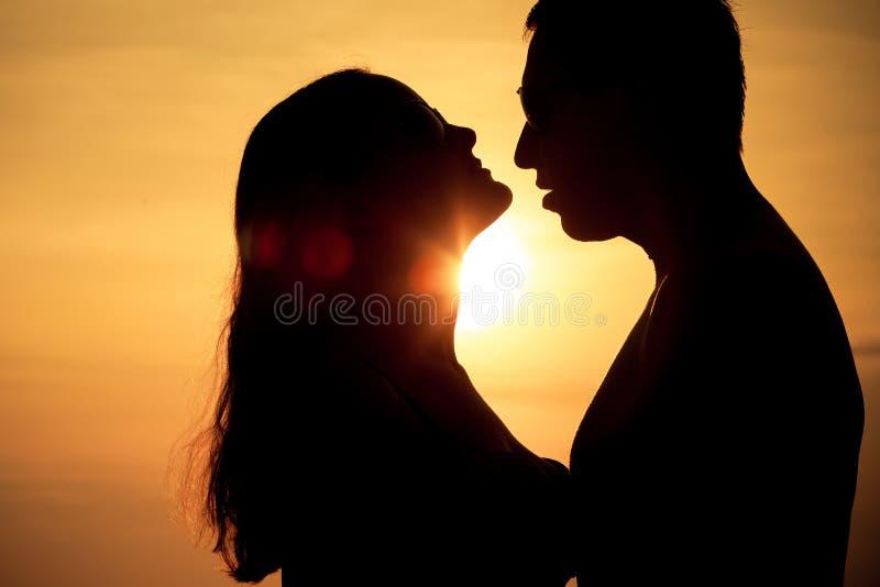 Пары в влюбленности подпирают светлый силуэт на море стоковая фотография