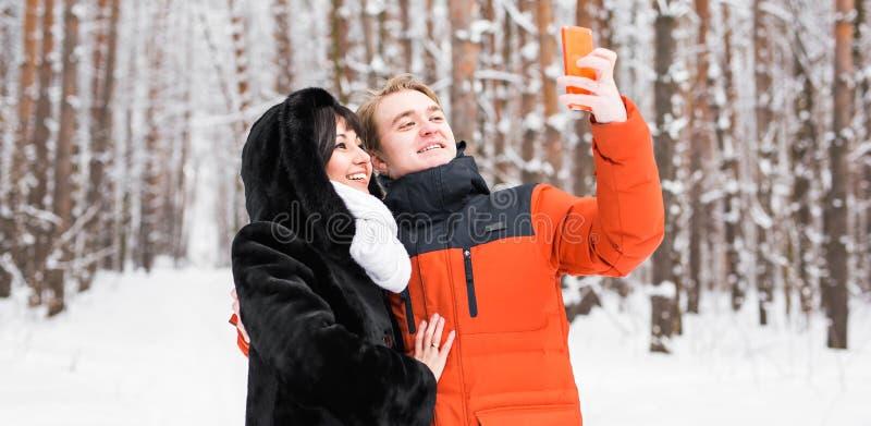 Пары в влюбленности усмехаясь и делая selfie в зиме outdoors стоковые фотографии rf