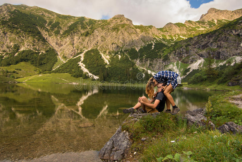 Пары в влюбленности целуя перед озером/парой горы целуя перед красивой панорамой с горами стоковое фото