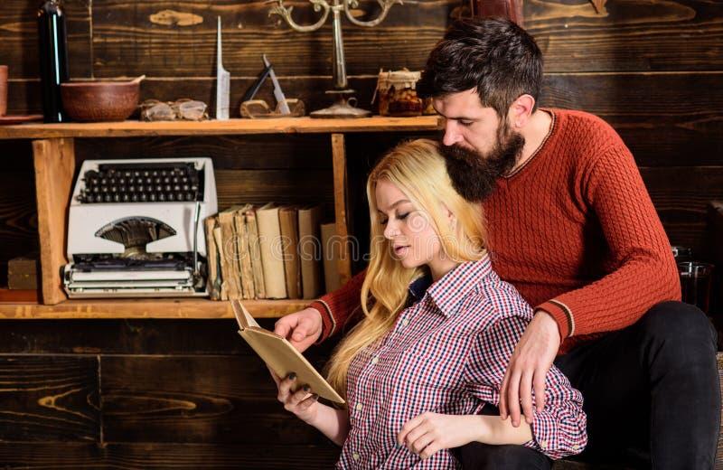 Пары в деревянном винтажном интерьере наслаждаются поэзией Романтичная концепция вечера Дама и человек с бородой на мечтательных  стоковые изображения rf