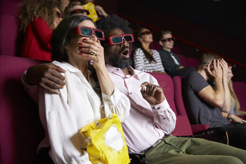 Пары в кино нося стекла 3D смотря фильм комедии стоковое фото rf