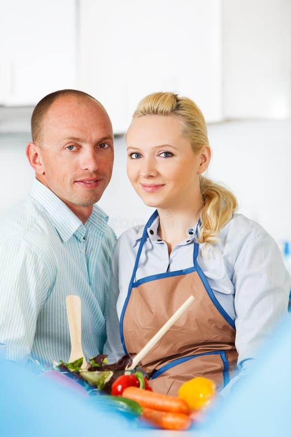 Пары в кухне подготовляя салат стоковые изображения rf