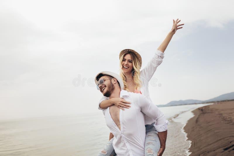 Пары в любов на летних каникулах пляжа Радостная девушка перевозить на молодом парне имея потеху стоковые изображения
