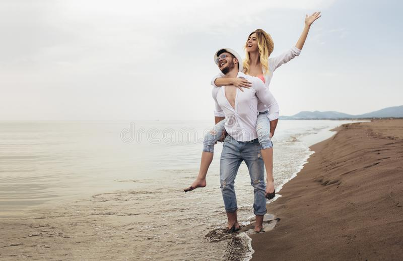 Пары в любов на летних каникулах пляжа Радостная девушка перевозя по железной дороге на молодом парне имея потеху стоковое фото rf