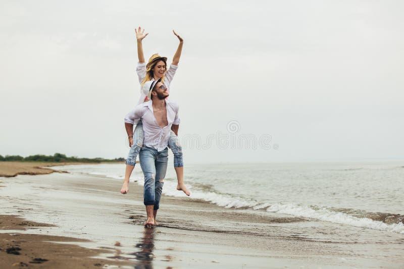 Пары в любов на летних каникулах пляжа Радостная девушка перевозя по железной дороге на молодом парне имея потеху стоковое изображение