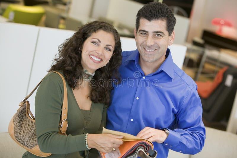 Пары в магазине смотря портрет образцов ткани стоковое фото