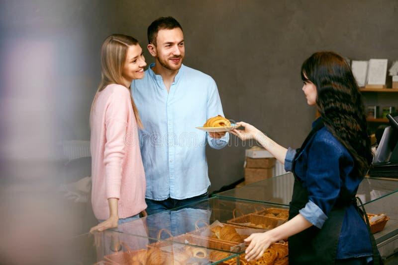 Пары в магазине хлебопекарни Красивые люди выбирая печенье стоковые изображения