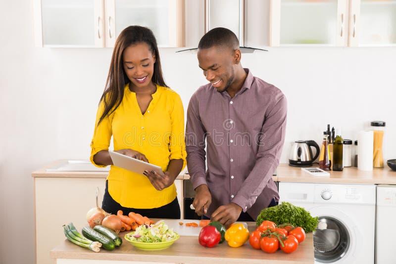Пары в домашней кухне используя электронную таблетку стоковые фотографии rf