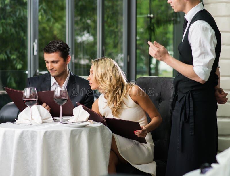 Пары в ресторане делая заказ стоковое фото