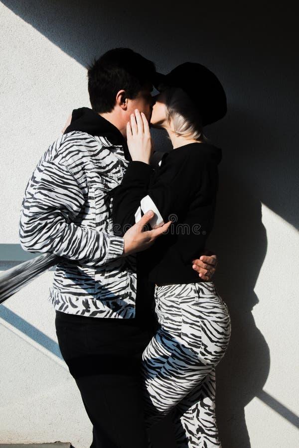 Пары в черноте и одежды печати зебры целуя в тени стоковая фотография rf