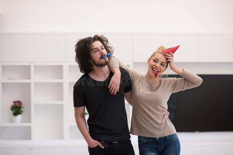 Пары в шляпах партии дуя в свистке стоковое фото rf