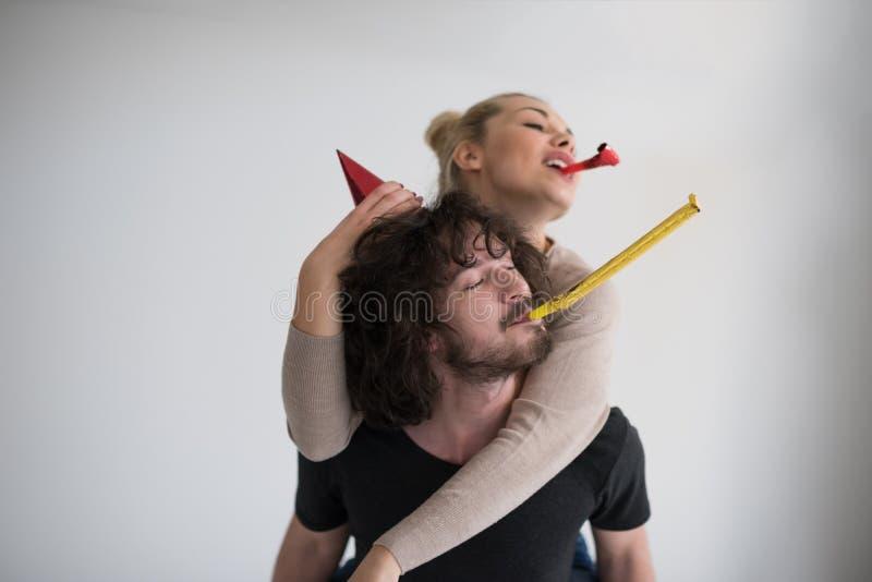Пары в шляпах партии дуя в свистке стоковое изображение
