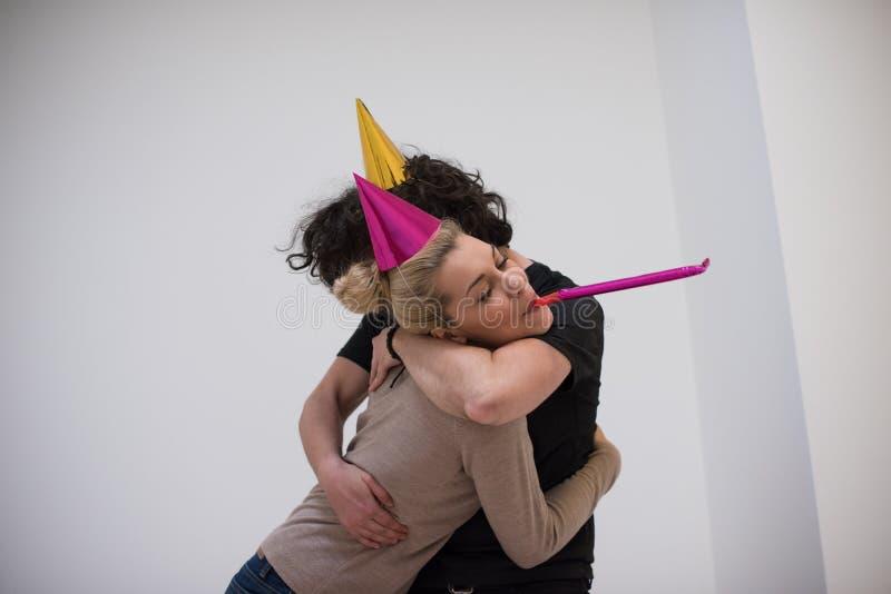 Пары в шляпах партии дуя в свистке стоковые фотографии rf
