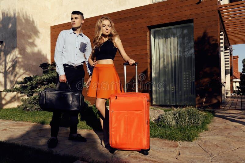 Пары в элегантных одеждах при сумки представляя в интерьере стоковое фото