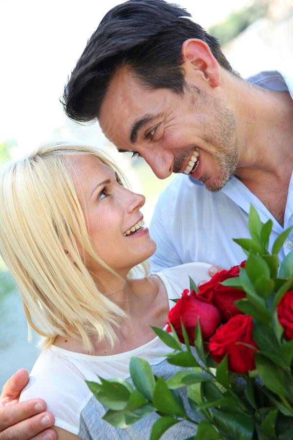 Пары влюбленн в красные розы стоковое изображение