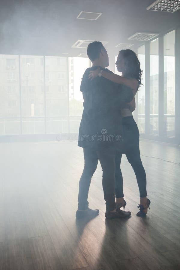 Пары в kizomba танцев любов в комнате танца полной дыма стоковое фото