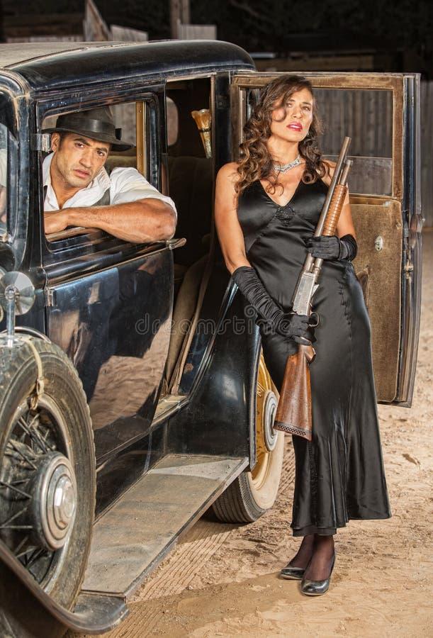 Пары гангстера с корокоствольным оружием в автомобиле стоковое изображение