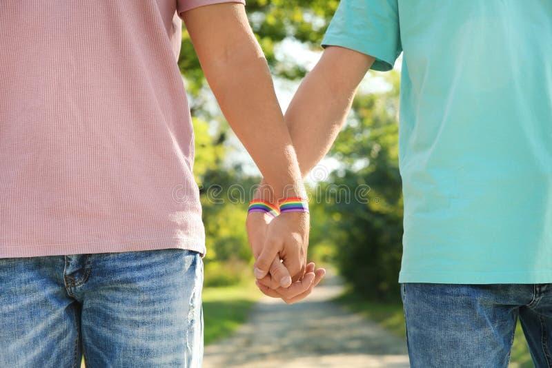 Пары гея с wristbands держа руки outdoors стоковые изображения