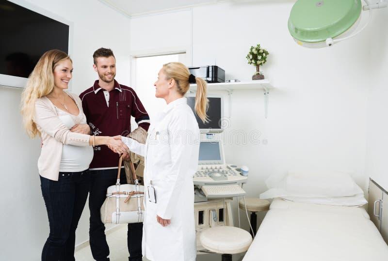 Пары гинеколога приветствуя счастливые молодые стоковое изображение