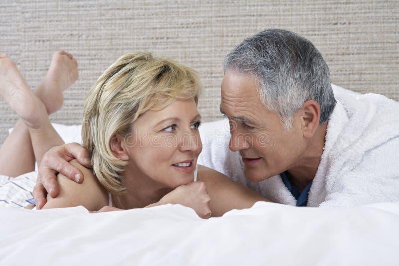 Пары говоря пока лежащ в кровати стоковая фотография rf