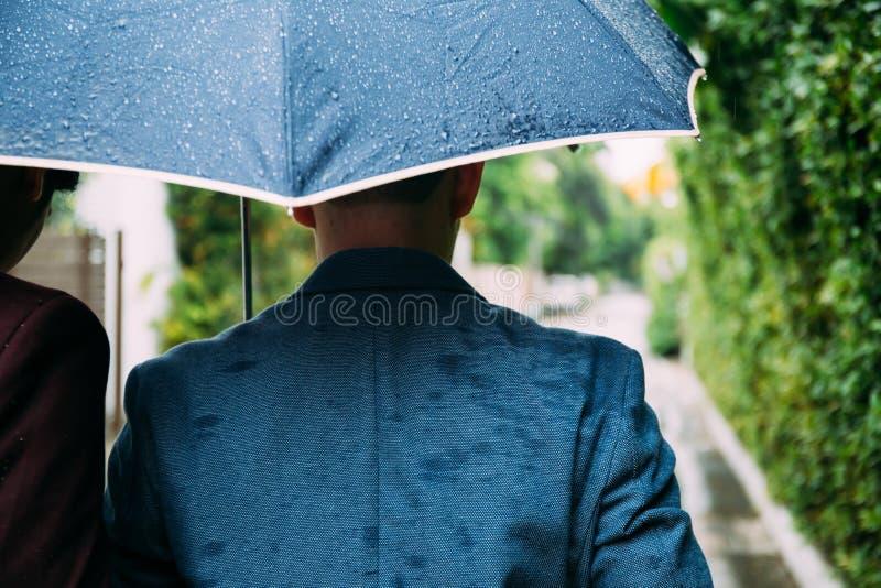 Пары гомосексуалиста держа зонтик и руки совместно Назад гомосексуальных людей идя в дождь стоковые фотографии rf