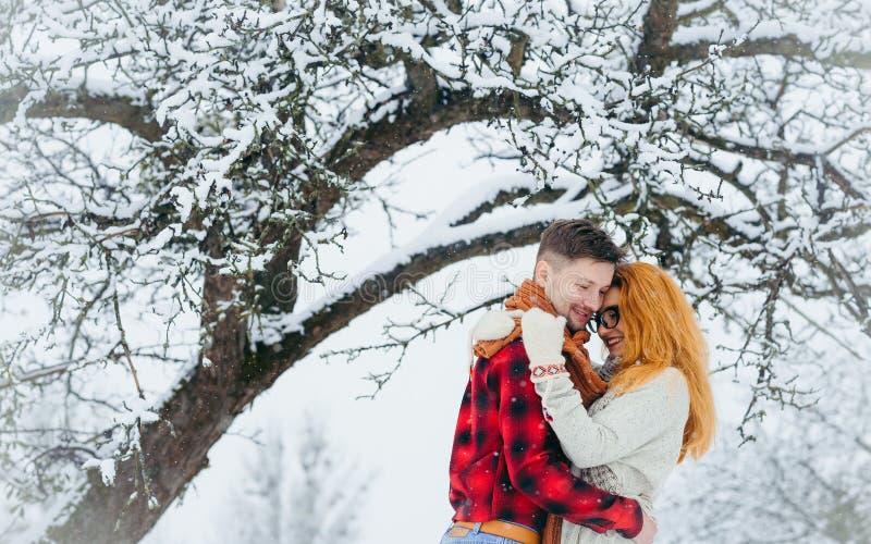 Пары горизонтального портрета конца-вверх счастливые обнимая влюбленность снега касающего леса снежностей сторон пушистую чувстви стоковое изображение