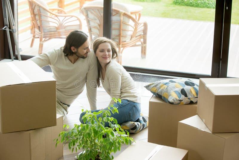 Пары двинули в новый дом сидя на поле с коробками стоковые фотографии rf