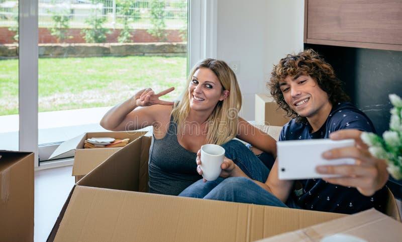 Пары делая selfie сидя внутри moving коробки стоковое изображение rf