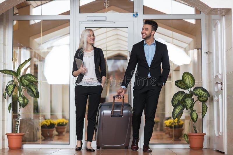 Пары дела в лобби гостиницы, человеке группы предпринимателей и гостях женщины приезжают стоковая фотография rf