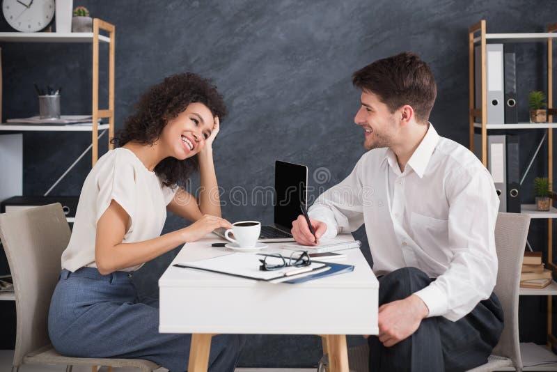 Пары дела сидя и говоря на современном офисе стоковые фото