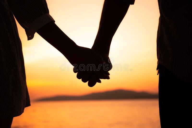 Пары держат руки летом на заходе солнца на пляже стоковое фото rf