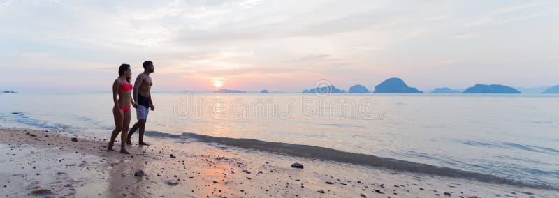 Пары держа руки идя на пляж на заходе солнца, молодом туристском человеке и женщине на празднике моря стоковые фото