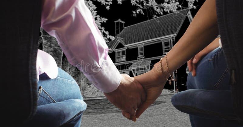 Пары держа руки перед эскизом чертежа дома стоковое изображение rf