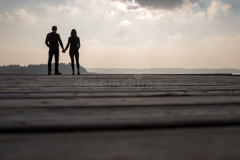 Пары держа руки пока стоящ против природы стоковое фото
