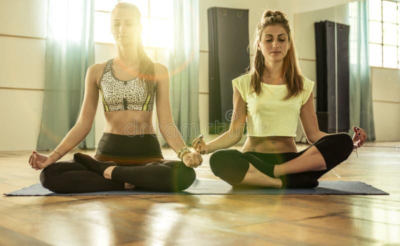 Пары девушек делая йогу стоковые фото