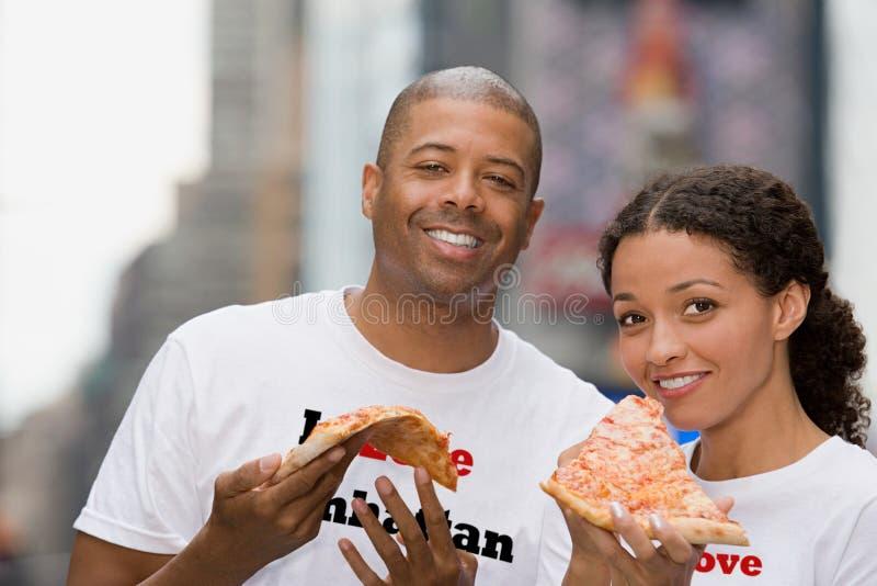 Пары держа пиццу стоковое изображение