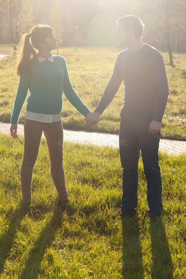 Пары держа руки на траве в парке стоковое изображение
