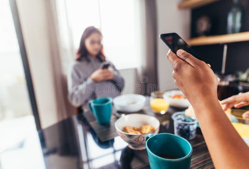 Пары есть завтрак пока использующ мобильные телефоны стоковое фото rf