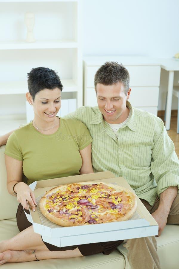 пары есть счастливую пиццу стоковая фотография