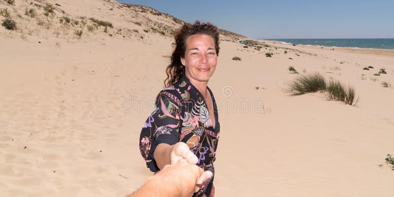 Пары женщины человека рук любя отдыхая на пляже на девушке солнечного дня хотят, чтобы ее человек следовать ей в заголовке шаблон стоковые фото