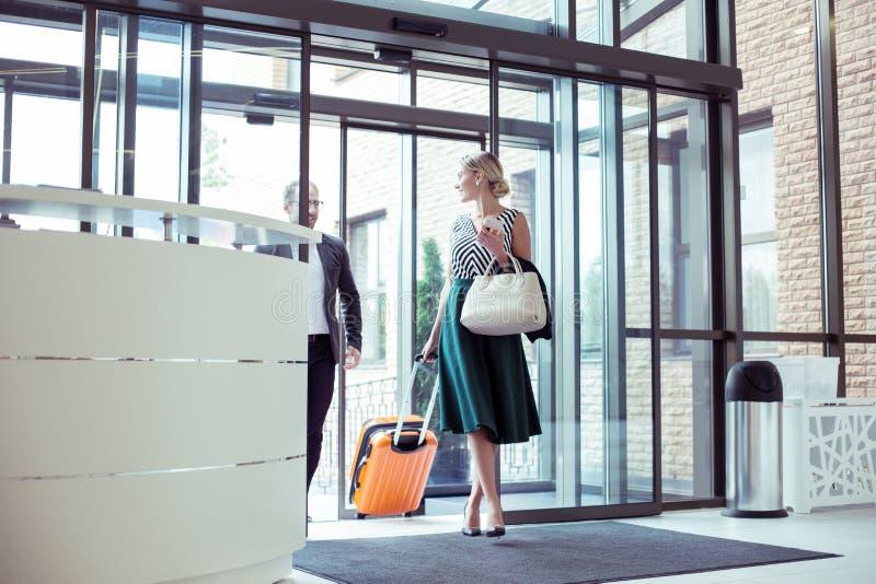 Пары зажиточных бизнесменов с гостиницой багажа входя в стоковые изображения rf