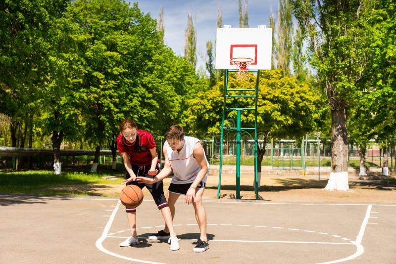 Пары играя баскетбол на внешнем суде стоковое изображение