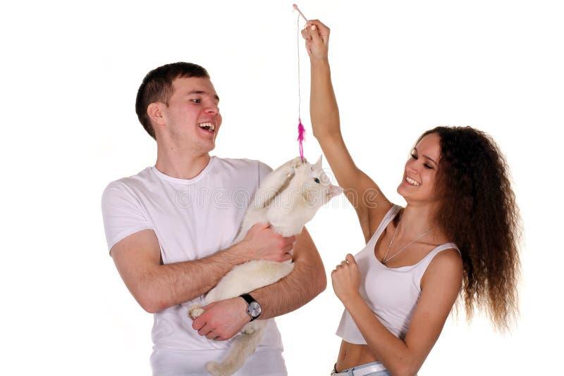 Пары играя с их котом стоковое изображение