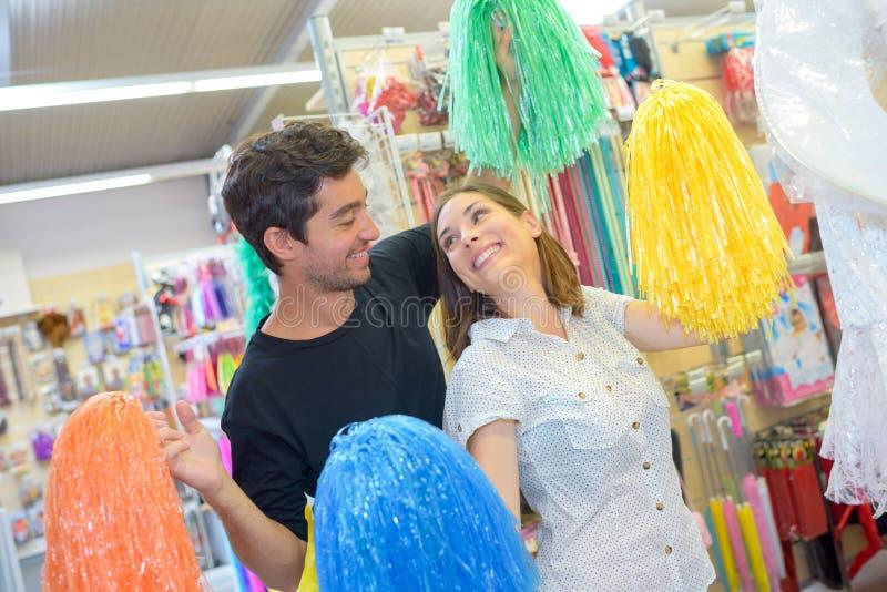 Пары играя с pompoms в магазине стоковые изображения