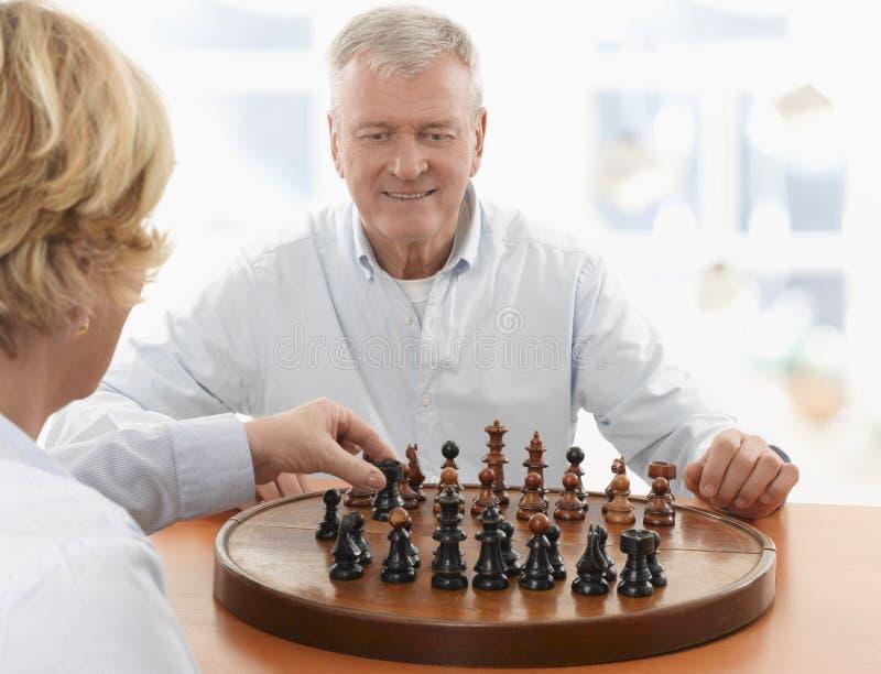 Пары играя шахмат в живущей комнате стоковое фото