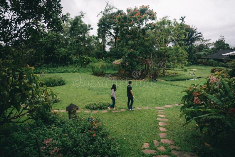 Пары идя в красивый зеленый парк стоковая фотография