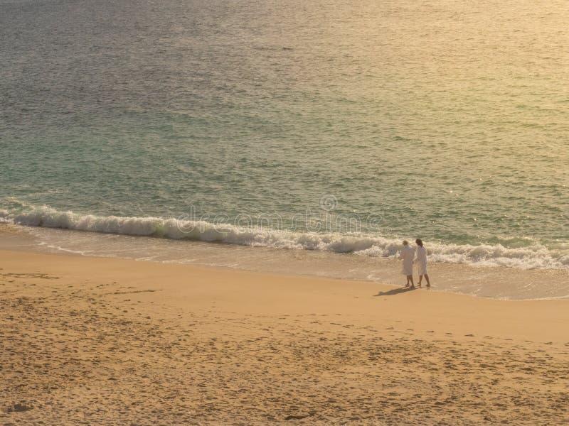 Пары идя на пляж с белым купальным халатом стоковые фото