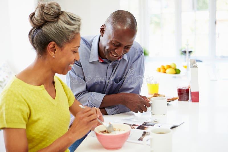 Пары имея завтрак и читая кассету в кухне стоковое изображение